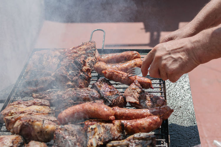 Close-up of hand holding barbecue grill