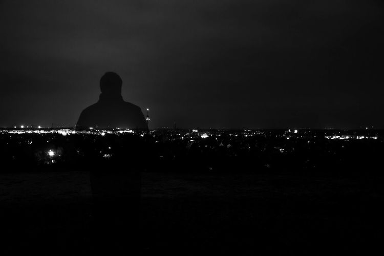 Rear view of silhouette woman against illuminated cityscape