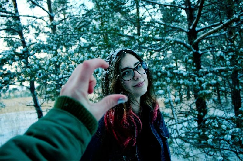 Cropped Image Of Hand Against Woman During Winter