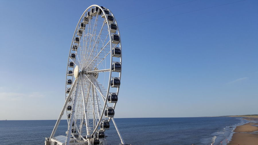 Low angle view of ferris wheel by sea against clear sky