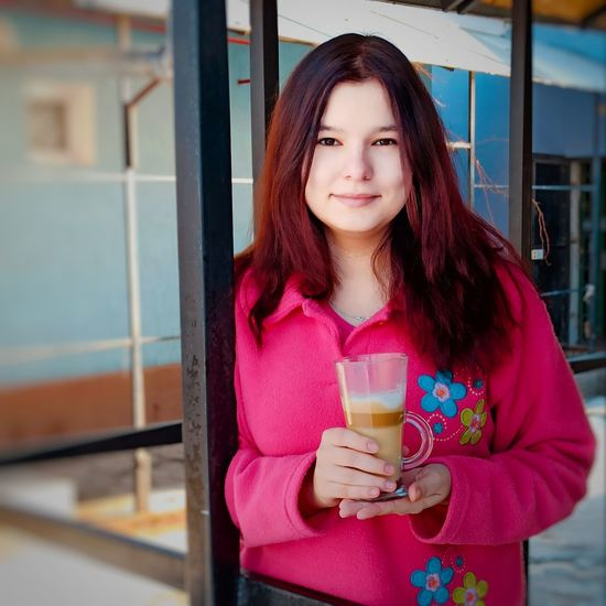 Portrait of beautiful young woman drinking glass