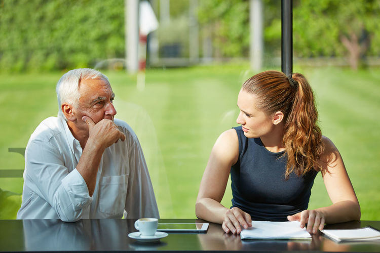 Senior Man Talking To Woman Sitting At Table