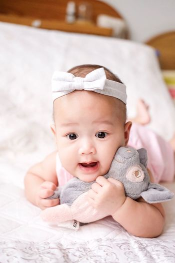 Cute Baby Girl With Soft Toy Lying On Bed At Home