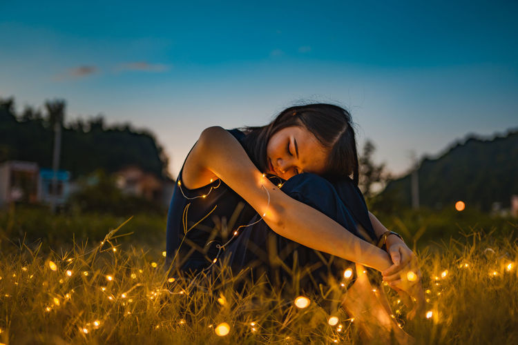 Woman with illuminated string light sitting on grass during sunset