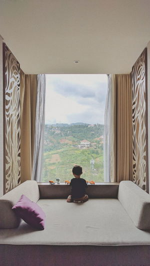 Rear view of baby boy by window at home