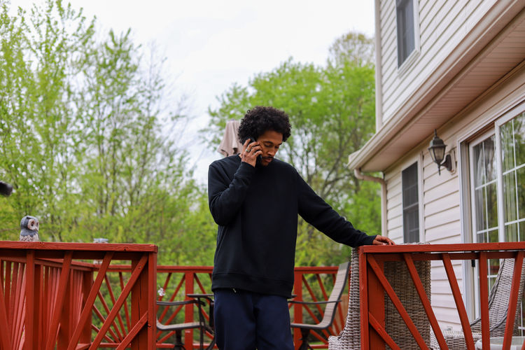 A portrait of an african-american man on his cellphone outdoors and sad
