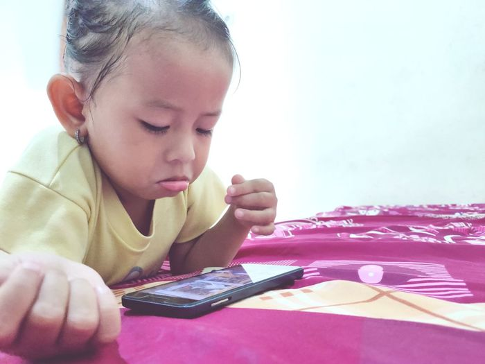 Cute boy using mobile phone on bed