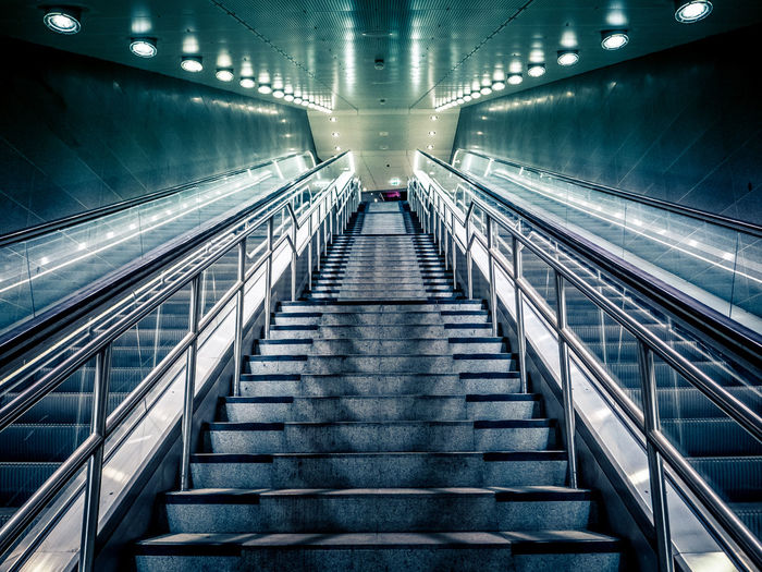 Low angle view of steps amidst escalator in illuminated subway station