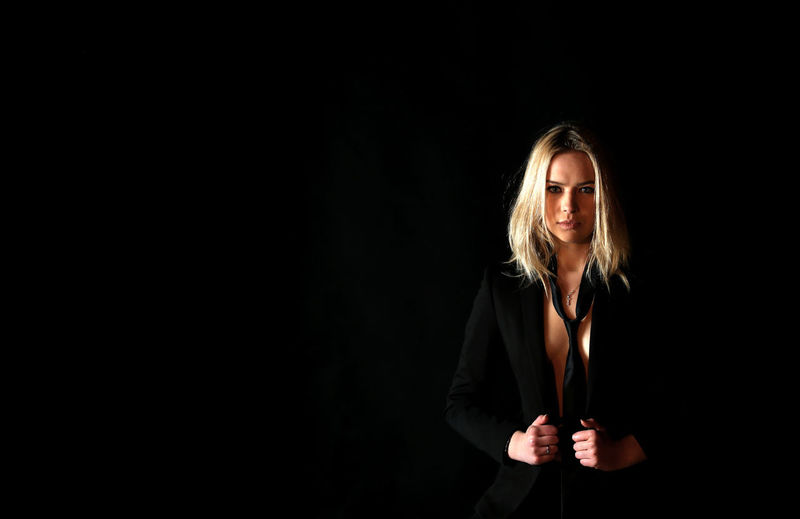 Portrait of woman wearing suit while standing against black background
