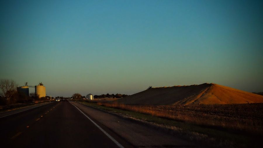 Road against clear sky at sunset