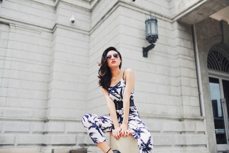 Woman sitting on bollard against building
