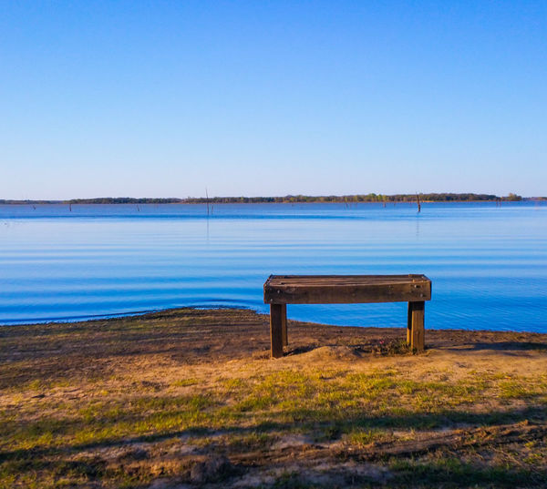 Empty wooden bench at lakeside