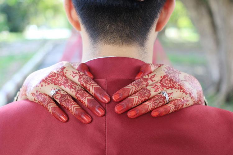 Cropped hands of bride around bridegroom neck during wedding ceremony