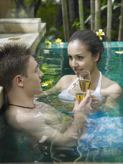 Close-Up Couple Having Drink In Swimming Pool