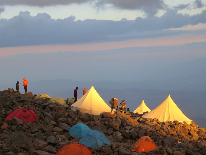 People by tents on rock against sky during sunset