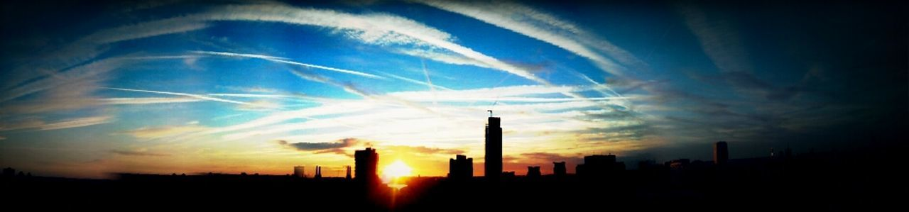 architecture, silhouette, building exterior, sunset, sky, built structure, skyscraper, city, cloud - sky, no people, modern, smoke stack, industry, cityscape, outdoors, urban skyline, factory, day