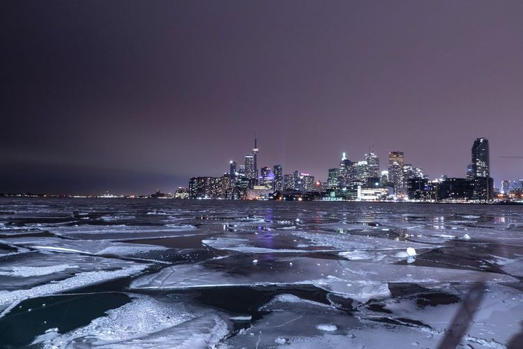 Illuminated buildings in city at night over frozen lake