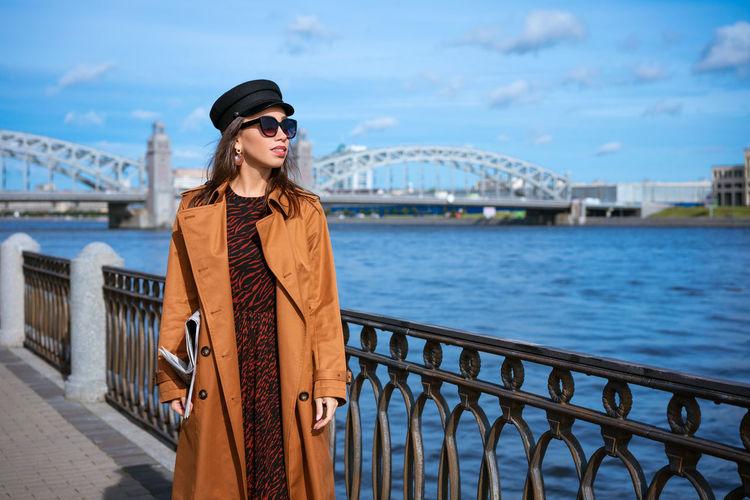 Woman standing by railing against bridge against sky