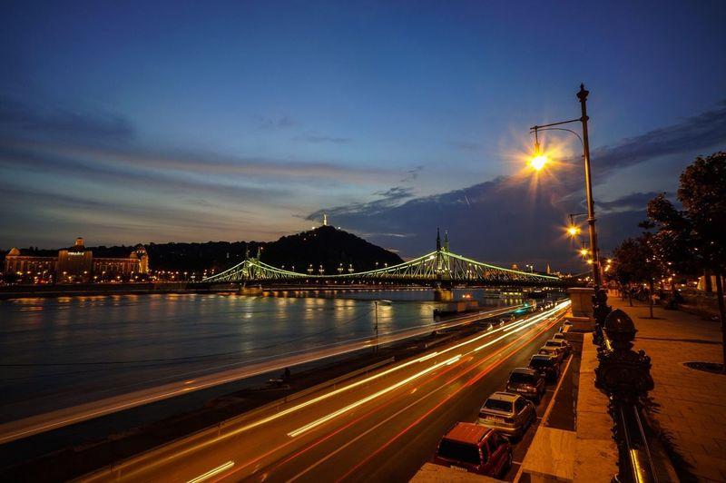 Illuminated Liberty Bridge And Street Against Sky At Dusk