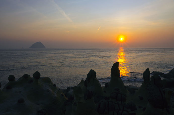 Twilight Coast Sunrise scenery, beautiful warm. Fishing Port Islands Keelung, Taiwan Twilight Beach Beauty In Nature Coastal Day Horizon Over Water Idyllic Nature Outdoors Rock - Object Scenics Sea Seaside Silhouette Sky Sun Sunlight Sunrise Sunset Tranquil Scene Tranquility Water