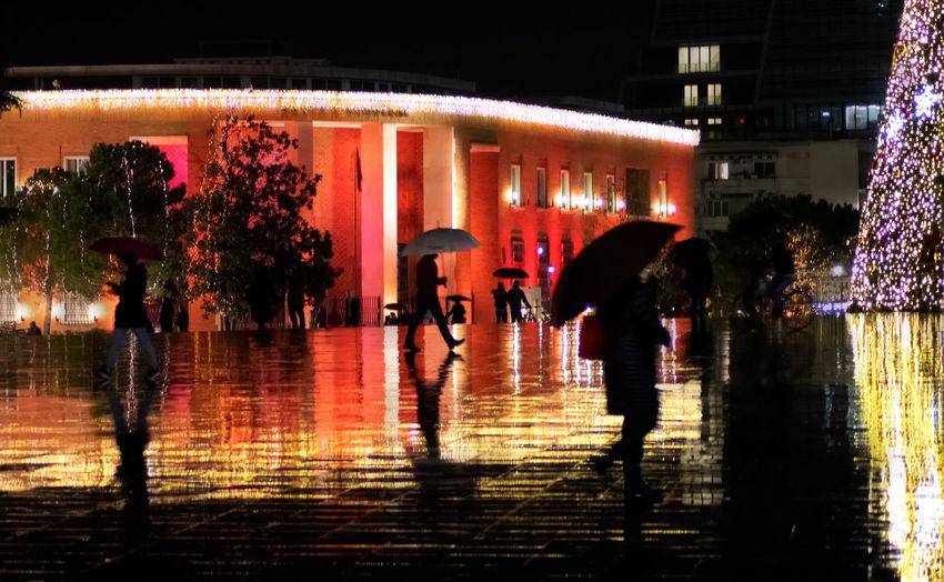 Silhouette people walking on wet street during rainy season at night