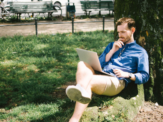 casual business in park Casual Clothing Communication Computer Connection Day Full Length Grass Laptop Leisure Activity Lifestyles Mid Adult Men Nature One Person Outdoors Park - Man Made Space People Real People Relaxation Sitting Technology Using Laptop Wireless Technology Young Adult Young Men