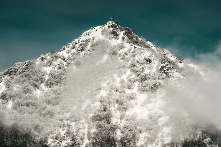 Low angle view of snowcapped mountain against sky