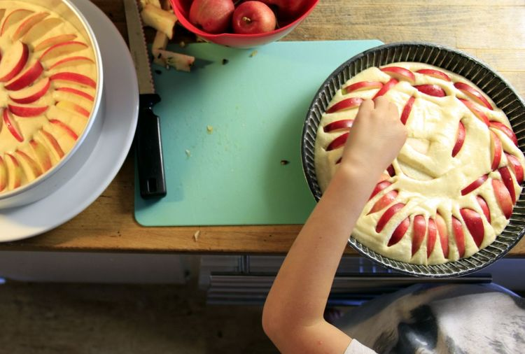 Cropped image of person making apple pie in kitchen