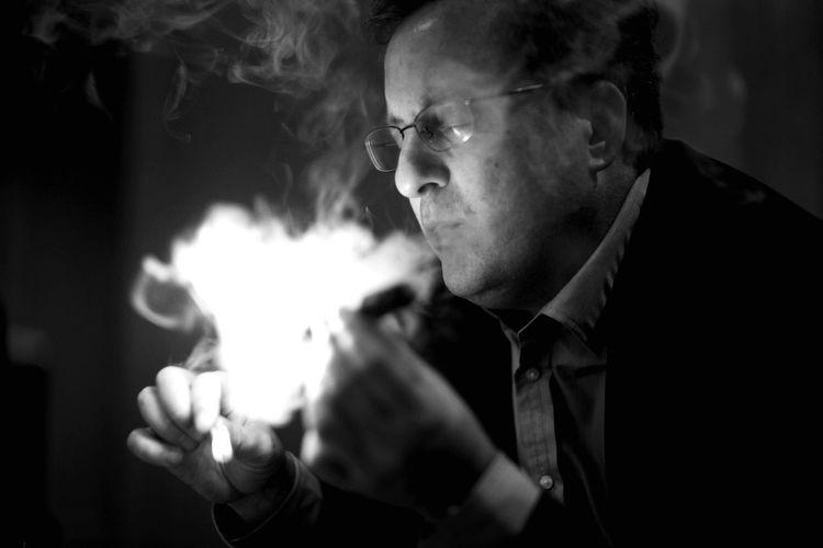 Man exhaling smoke in darkroom