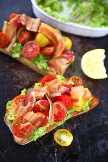 Avocado toast with cherry tomatoes and bacon Food Freshness Healthy Eating No People Ready-to-eat Indoors  Close-up Snack Breakfast Bacon Cherry Tomatoes Avocado Toast  Mashed Avocado Lemon Overhead View Homemade Food Vertical Studio Shot Supper Light Meal Brunch Colorful Fresh Produce