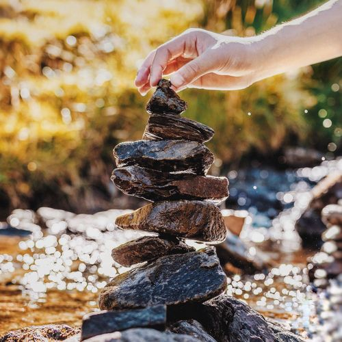 Zen Focus On Foreground Stack Close-up Person Day Group Of Objects Outdoors Stone Sunset Beauty In Nature Heaven Nature Solitude Exploration Non-urban Scene River Water Tranquility Tranquil Scene Remote Countryside Beautiful Bokeh Relaxation