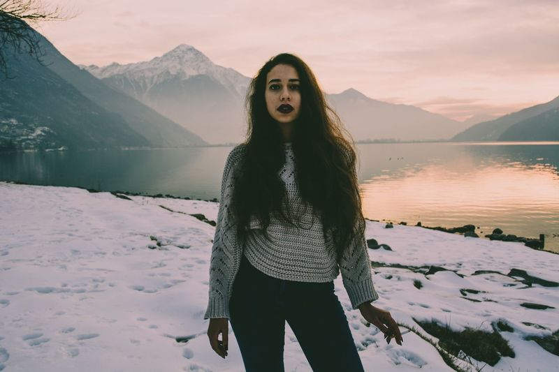 Portrait of woman standing by lake against mountain during winter