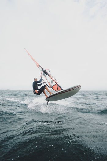 Man windsurfing in sea against sky