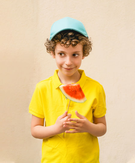 Smiling boy holding watermelon while standing against wall