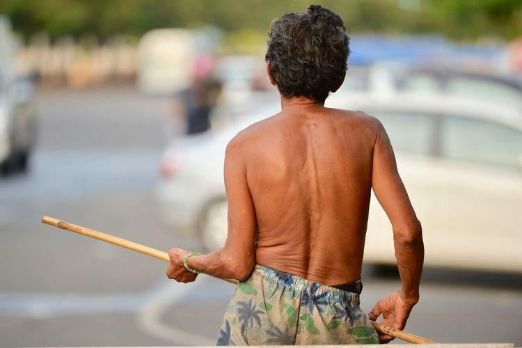Rear view of shirtless man holding stick