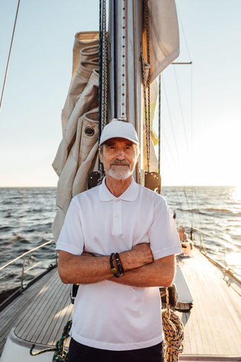 Portrait of senior man standing on sailboat against sky