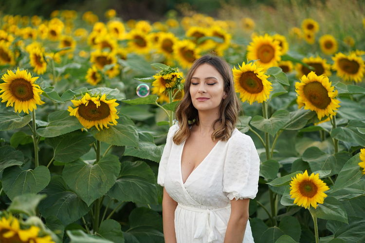 Beautiful young woman standing by sunflowers on field