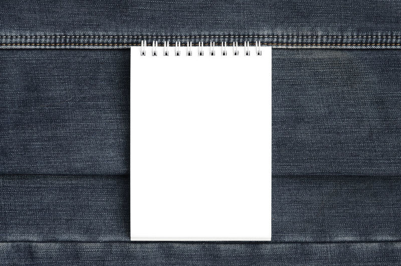 Directly above shot of spiral notebook on jeans