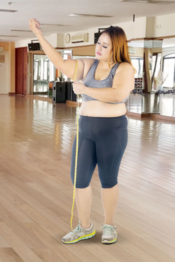 Woman measuring arm with tape measure while standing in gym