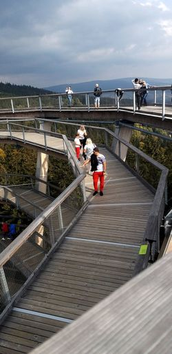 People on footbridge by sea against sky