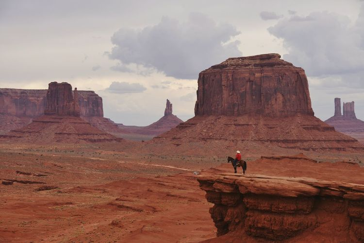 View of man on rock against cloudy sky