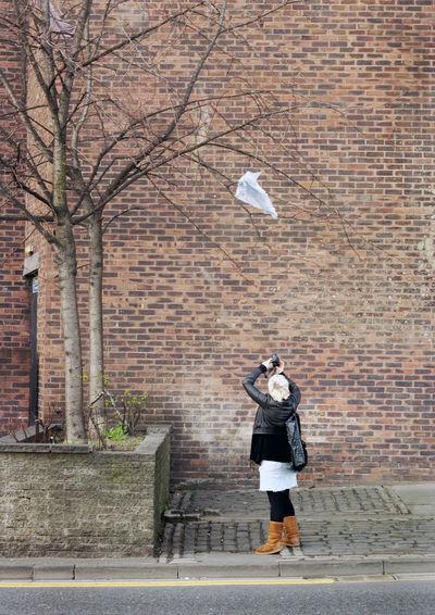 Woman capturing image of tree on camera