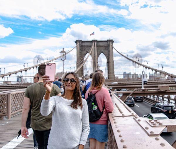 Smiling mid adult woman taking selfie on brooklyn bridge
