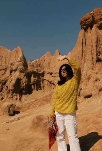 Woman shielding eyes while standing against rock formations