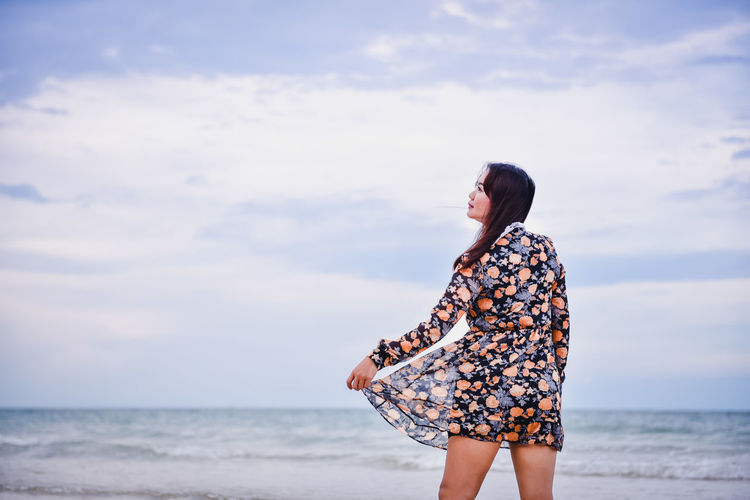 Woman wearing dress standing at beach against sky