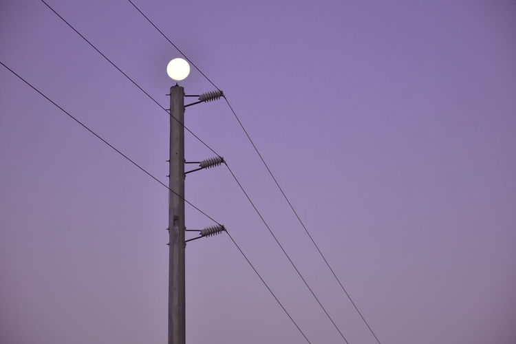 Low angle view of electricity pylon against clear sky at dusk