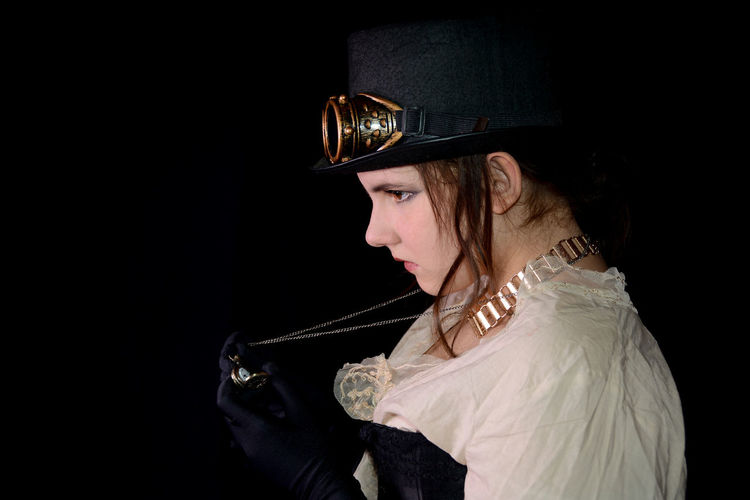 Young girl in steam punk look, from the side, looks at her watch, with black background