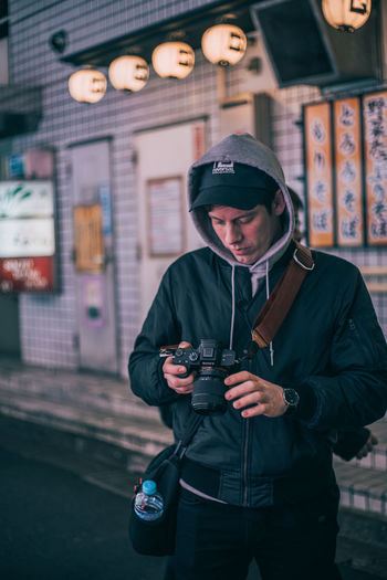 Japan Foreigner Portrait Using Technology Using Using Camera Camera Photographer Working portrait of a friend Candid Nightphotography Night Photography One Person Camera - Photographic Equipment Standing Holding Young Adult Photography Themes Three Quarter Length Front View Technology Real People Focus On Foreground Clothing Young Men Lifestyles Photographic Equipment Leisure Activity Photographing Warm Clothing Digital Camera Outdoors