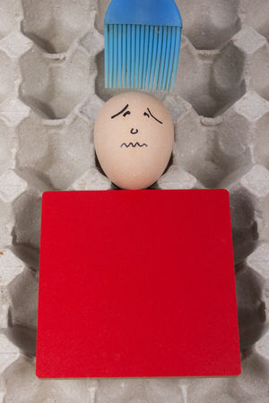 Cartoon face expression at egg and red board with finger also plastic brush Angry; Anthropomorphic Face Anthropomorphic Smiley Face Blue Brush; Blue Plastic Brush; Brush; Close-up Confuse; Excited; Expression; Food Indoors  Joke; No People Plastic; Sad; Scare; Shy; Sick