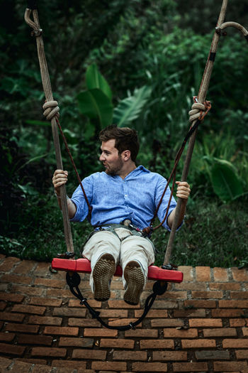 Man sitting on swing at playground
